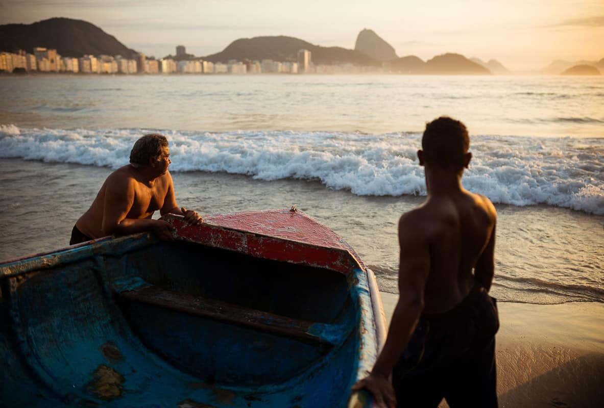 Fishermen taking their boat out at dawn, Copacabana, Rio de Janeiro, Brazil