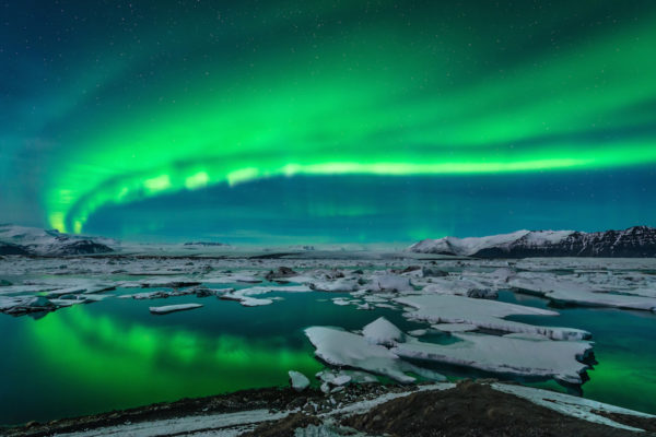 Spectacular auroral display over the glacier lagoon Jokulsarlon in Iceland.