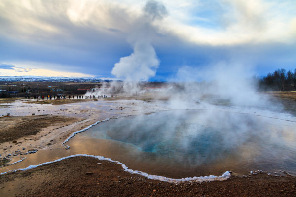 Blue pool at the Haukadalur geothermal area, part of the golden circle route, with the Strokkur Geyser in the background in Iceland
