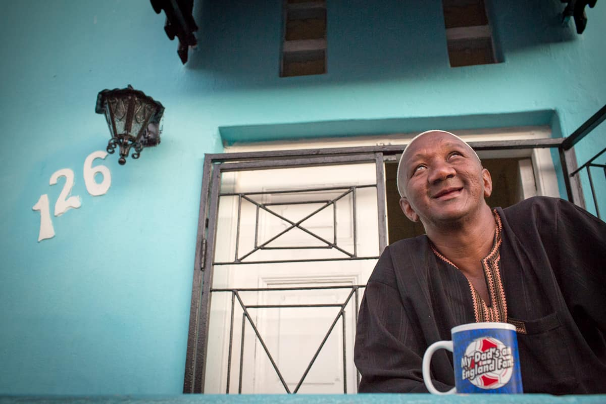 A man drinking a hot drink outside his blue home in Bo-Kaap by Sarah Isaacs