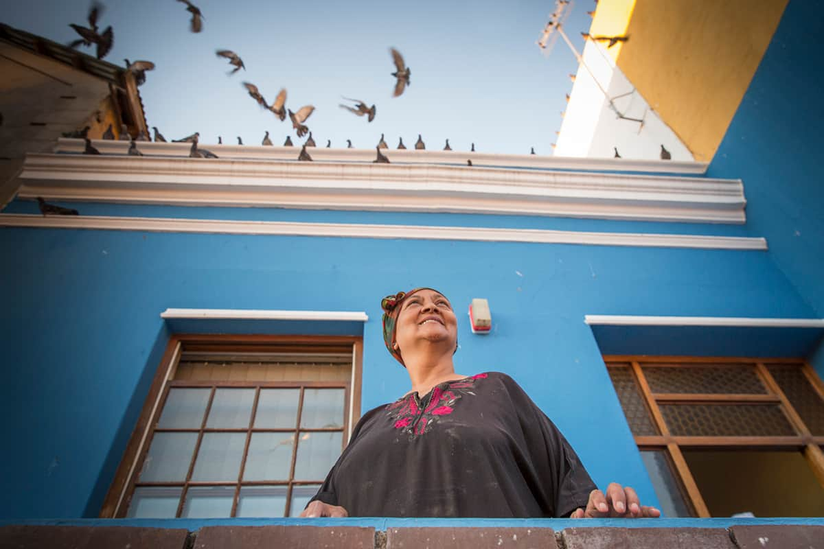 A woman standing out on her porch and looking up into the sky as birds fly over her blue house in Bo-Kaap by Sarah Isaacs